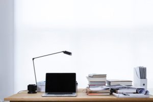 Desk table lamp laptop books stacked