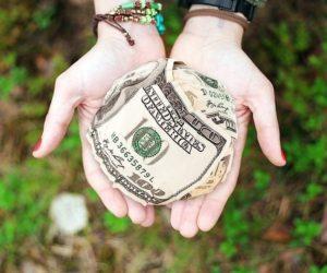 hands holding ball of money