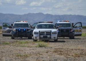 police cars on dirt road moutain background