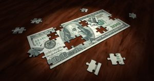 100 dollar bill puzzle on wood background
