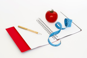 red journal measuring tape and tomato