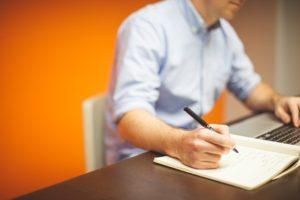 orange background man at desk