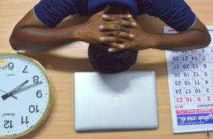 head on desk laptop clockface