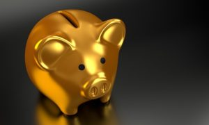 gold piggy bank on gray background