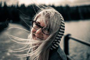 Blonde woman black glasses smiling