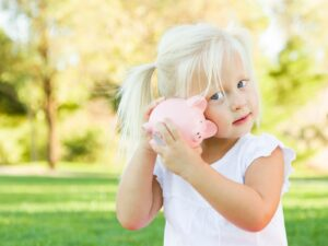 Blonde child with piggy bank