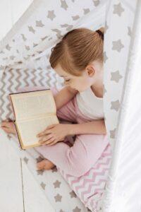 girl reading in star print tent